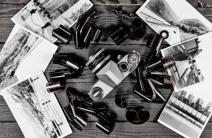 A flat lay of film rolls, camera and printed photos - developing film at home
