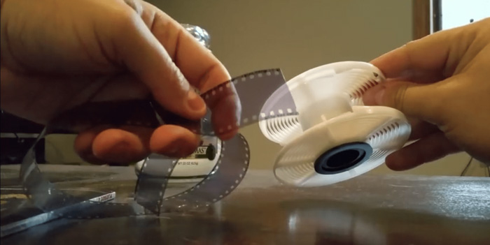 A close up of a photographer showing how to develop film at home