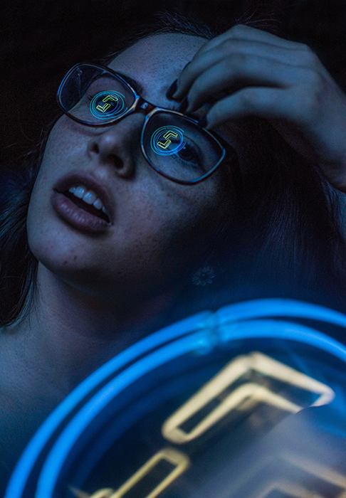 An atmospheric neon photography portrait of a female model with neon lights reflected in her glasses