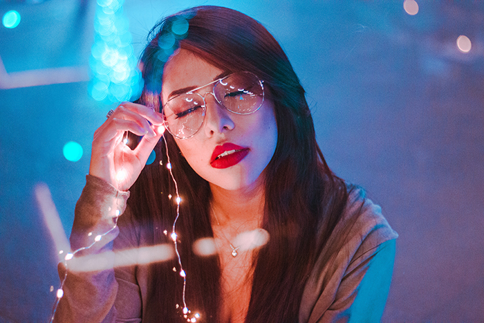 Atmospheric portrait of a female model holding fairy lights shot using neon photography