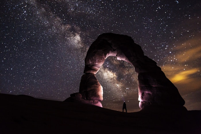 Uma deslumbrante imagem fotográfica noturna com um homem sob um arco de pedra e um céu estrelado.
