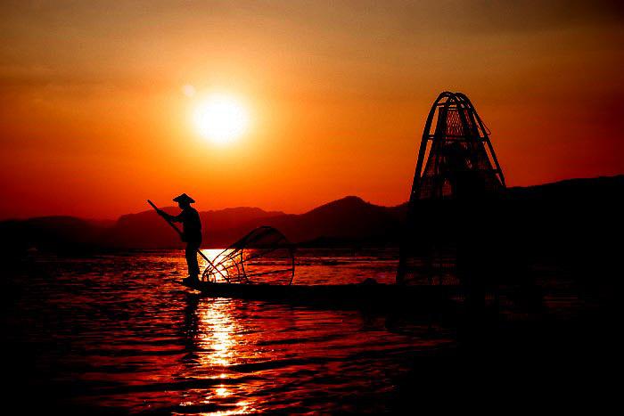 A portrait of fishermen on Inle Lake in Myanmar at sundown