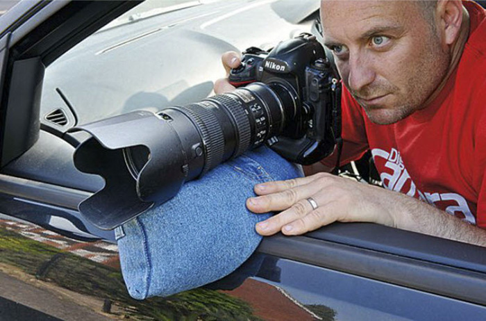 A photographer taking a shot out of a car window using a beanbag as a tripod - diy photography hacks