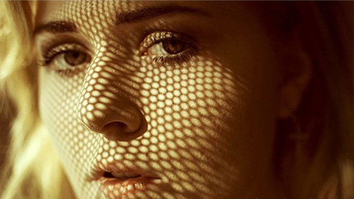 A portrait shot of a female model with shadows cast accross her face from a sifter - diy amazing photo hacks
