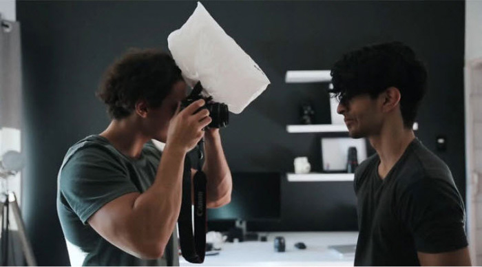 A photographer shooting a portrait of a male model in a studio using a plastic bag as a softbox