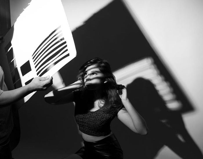 A black and white portrait of a model, with a person holding a cardboard sheet with holes cut in it to create shadows - photography hacks