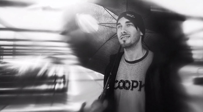 A street photography portrait of a man carrying an umbrella with a vignette effect made from Vaseline - diy photography hacks