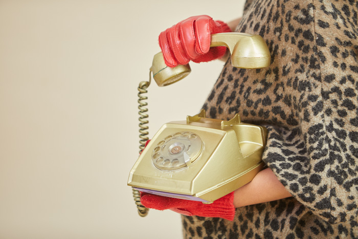A close up portrait of a woman in red gloves holding a red telephone