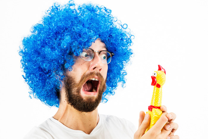 A humorous portrait of a man in a blue wig holding a rubber chicken - photoshoot ideas