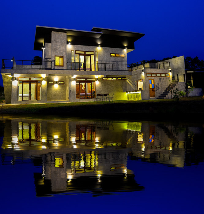 A large building reflected into a pond at night - photoshoot ideas