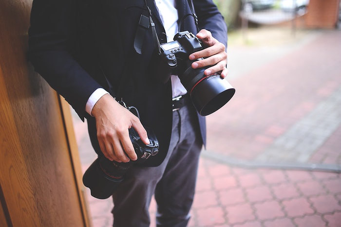 A close up of a professional photographer holding a DSLR at a photo shoot
