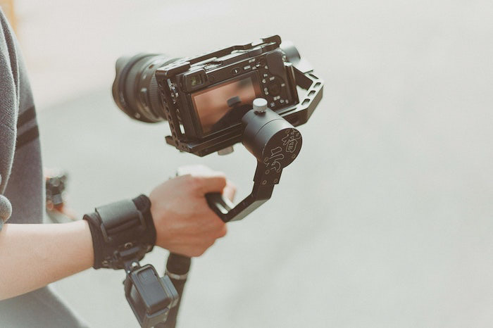 A bright and airy photo of a photographer holding a DSLR camera on a tripod