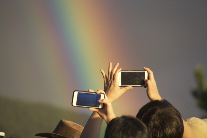 Two people taking rainbow photography with their smartphones