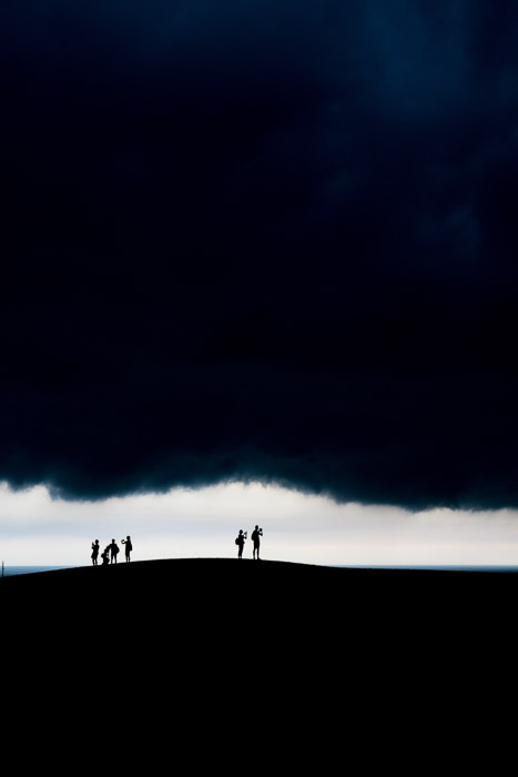The silhouettes of people amongst a dramatic evening landscape