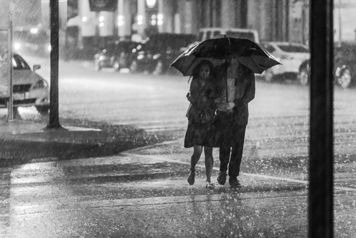 A candid street portrait of a couple walking through the rain with an umbrella
