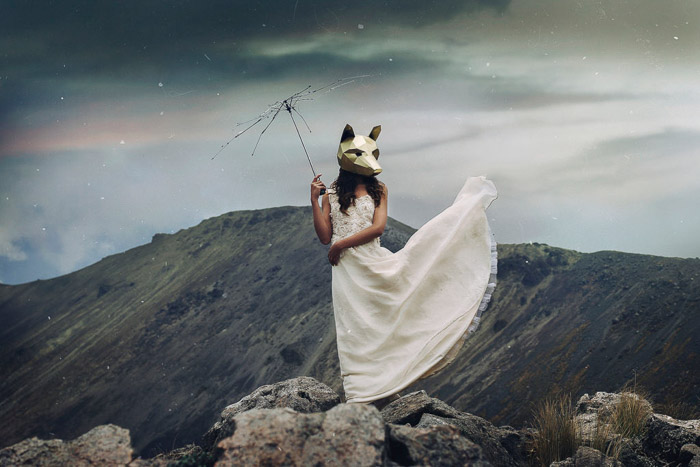 a conceptual porttrait of a female model in awolfmask, standing in a mountainous landscape - types of portrait photography