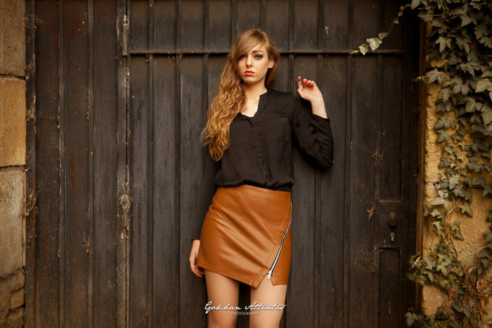 An environmrntal portrait of a femal model leaning against a wooden barn door- types of portrait photography