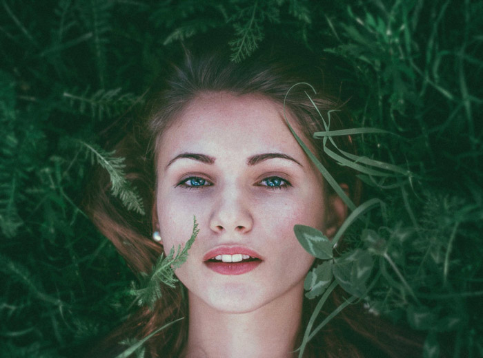 A fine art style photo of a femal model lying in foliage- types of portrait photography