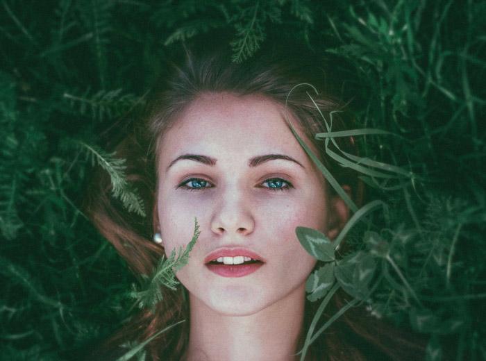 A fine art style photo of a femal model lying in foliage