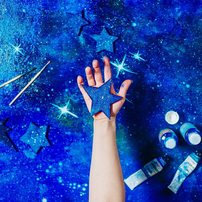 A creative spaced themed photography flat lay on a hand painted background