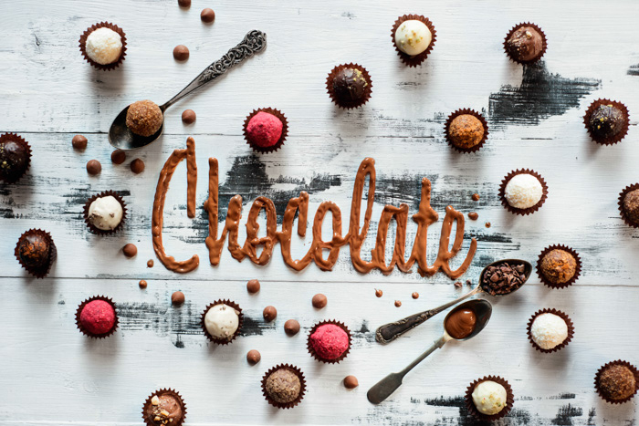 A creative flat lay ofchocolates and the word 'chocolate' spelled with food typography hand painted background