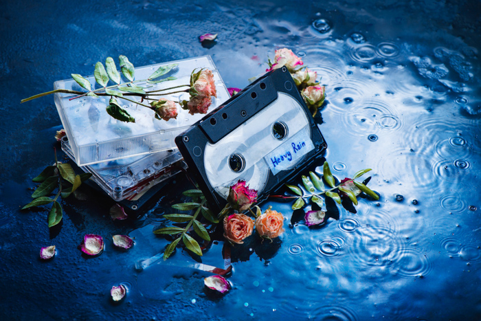 A creative flat lay of flower petals and cassette tapes on a hand painted background