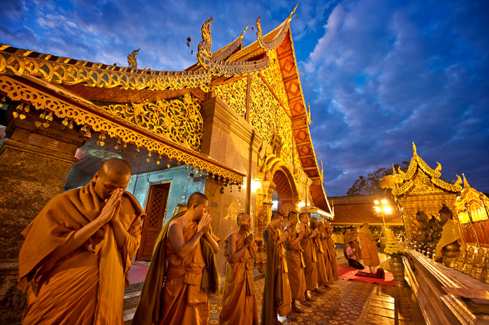A line of Buddhist monks praying outside a temple at dusk - shallow vs deep depth of field