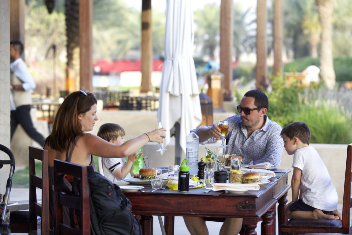 A family portrait eating dinner outdoors on holiday