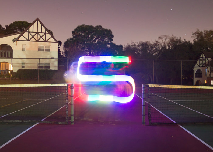 A colorful S shaped streak of light painting shot under on a tennis court at night using LED light painting tools