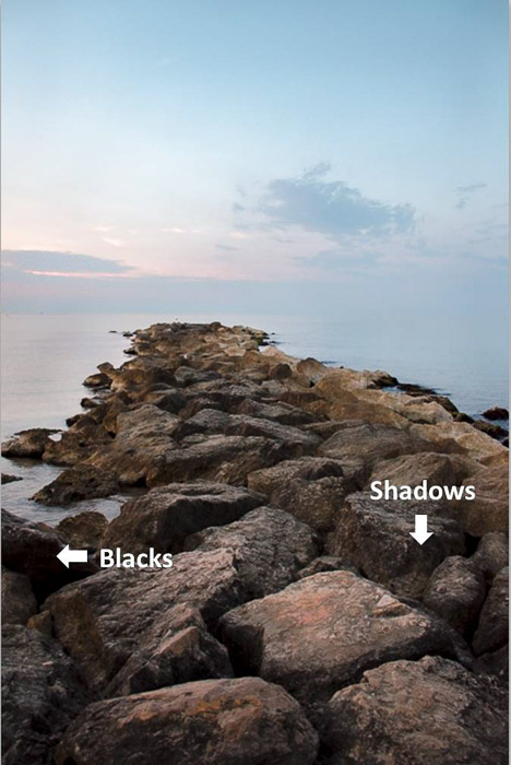 A stunning coastal landscape with arrows pointing out shadows and blacks in the rocks