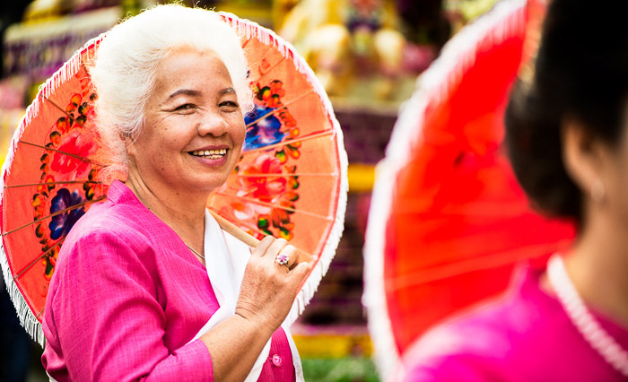 A colorful street portrait of an Elegant Senior Woman holding an umbrella - tips on using photos that tell a story