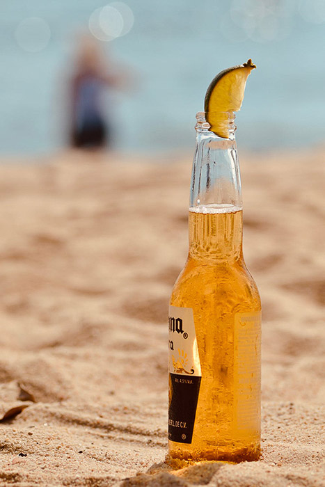 A bottle of corona beer with lime on a beach - how to photograph beer