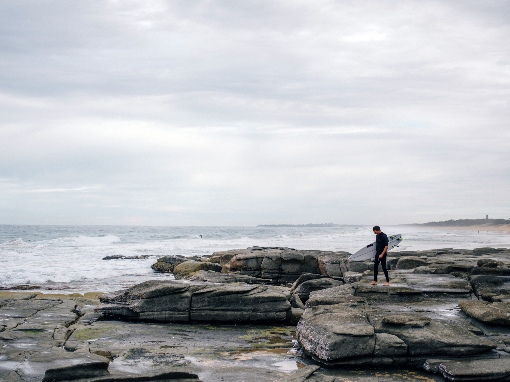 How to Do a Bend and Warp Trick in Photoshop - a surfer walking on rocks by the coast