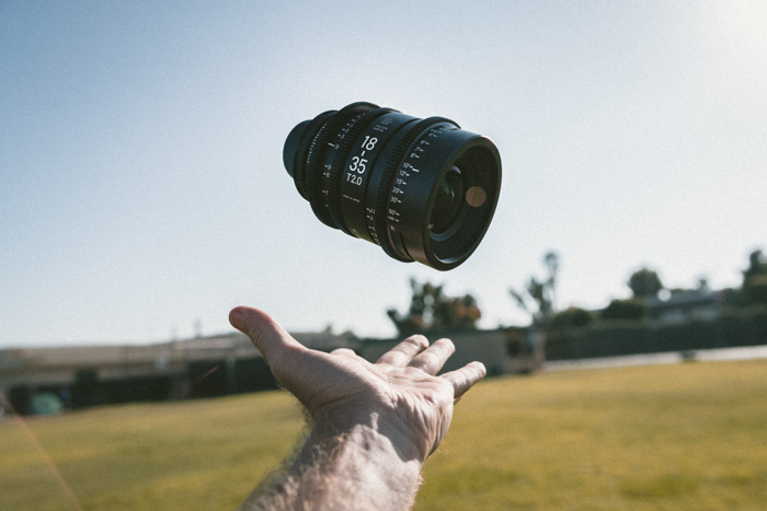 A close up of a photographer playfully throwing a camera lens into the air
