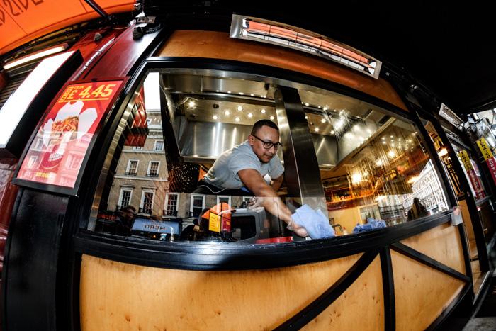 A fisheye portrait of a street food vendor at night