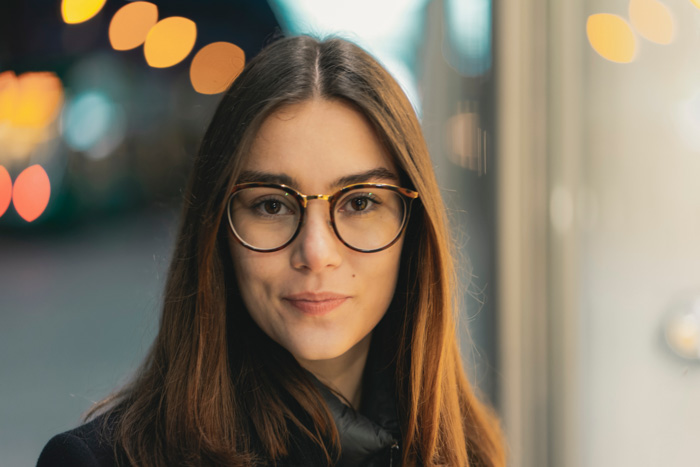 A portrait of a female model in glasses with a blurry bokeh background - camera lens guide
