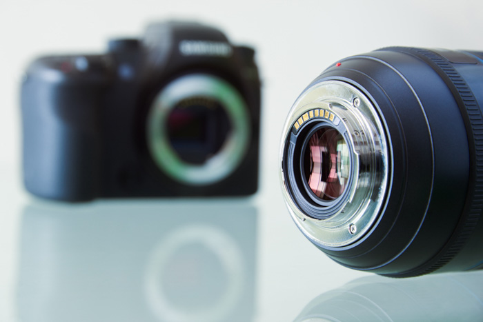 A camera lens in the foreground of a blurry dslr camera body - a guide to camera lenses