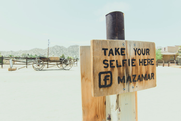 A wooden sign reading 'take your selfie here' in front of a dusty landscape