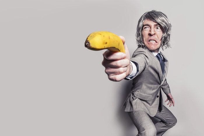 A humorous photo of a man holding a banana like a gun, his body shape distorted due to lens aberrations
