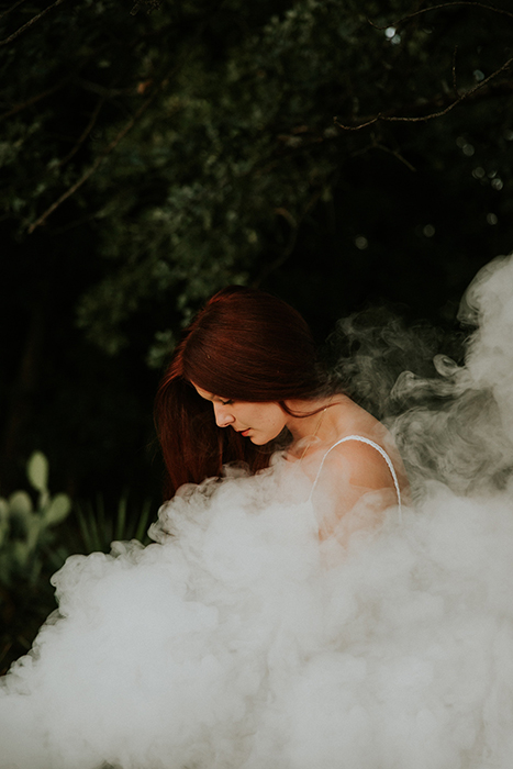 Dreamy portrait of a female model posing outdoors surrounded by smoke and dreamy background