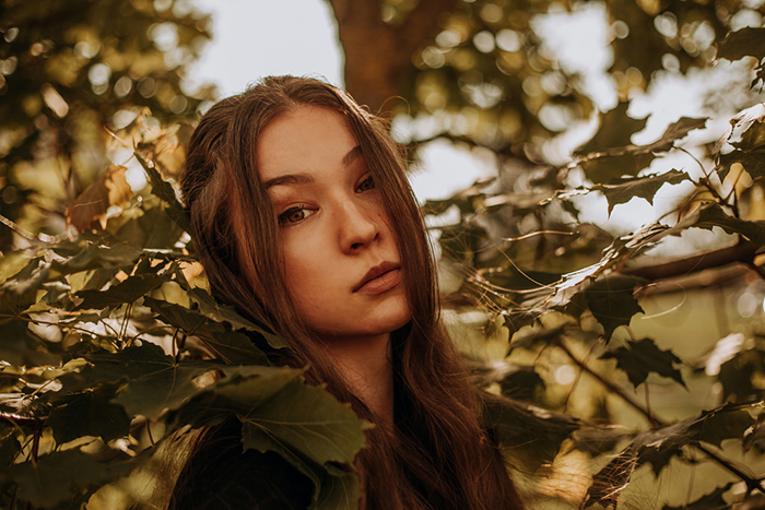 Dreamy photography shot of a female model posing outdoors among leaves - ethereal portraits