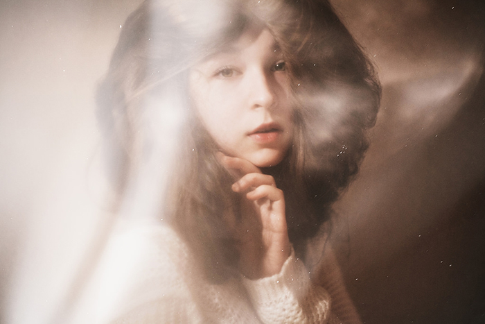 Dreamy portrait photo of a female model posing indoors in soft light
