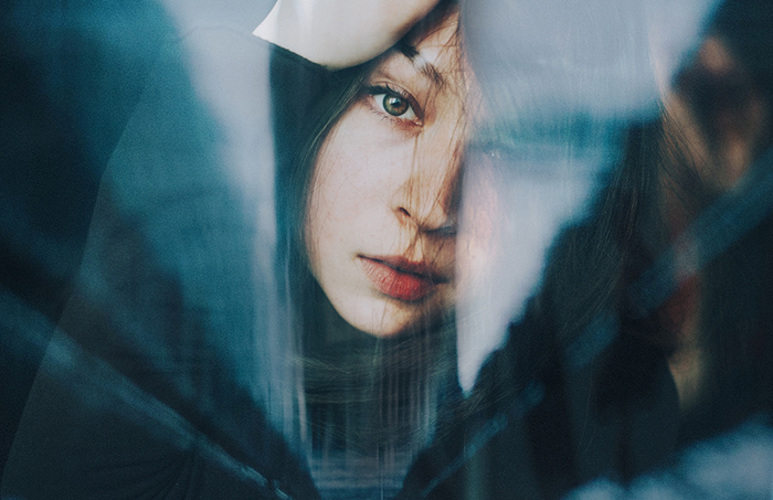 Ethereal portrait of a female model posing against a reflective surface with dreamy background