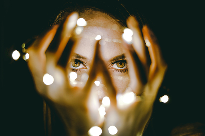 Atmospheric portrait of a female model holding a string of lights - fairy light photography