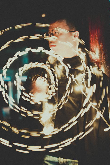 creative long exposure portrait of a man posing outdoors, with circles of fairy lights in front of him