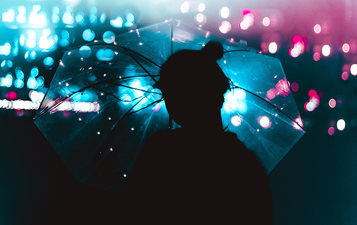 atmospheric silhouette of a female model holding an umbrella in the rain - fairy light photography