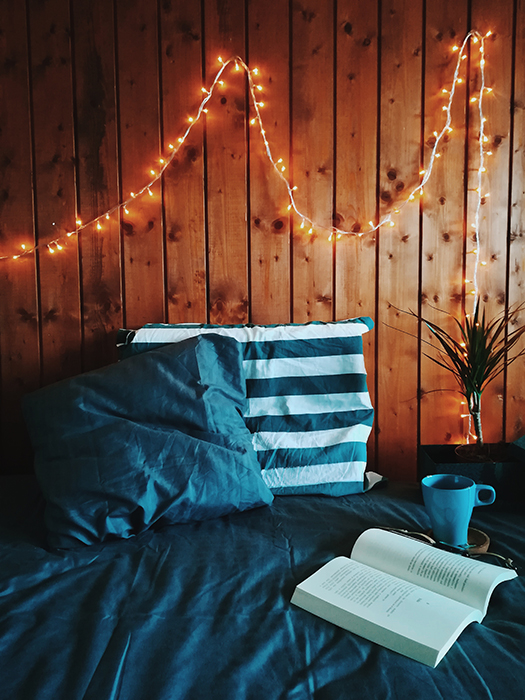 A still life shot of a book and cup on a bed with fairy lights on the wall - fairy light photography