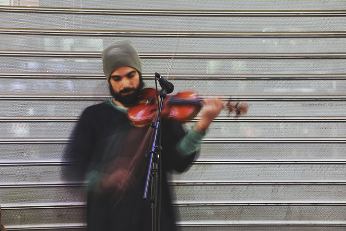 Blurry portrait of a street performer playing violin - fine art photography mistakes