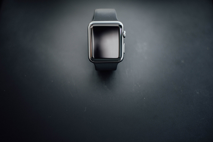 Overhead product shot of a black watch on a black background