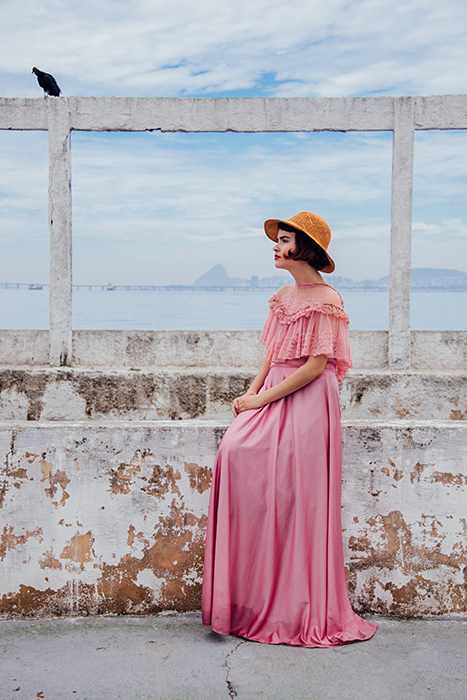 A female fashion model posing outdoors in vintage pink dress